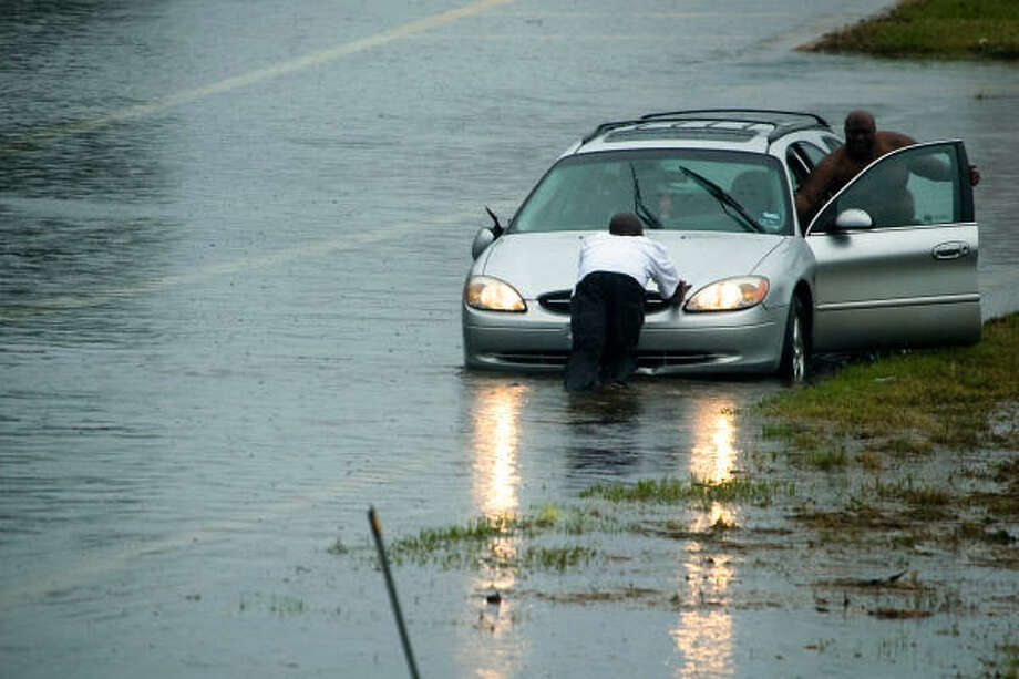 Motorists push a vehicle from high water on the North 610 Loop service road in Houston. Photo: Smiley N. Pool, Chronicle