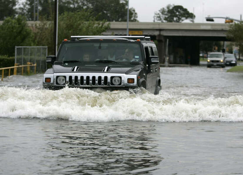 Alex San Miguel drives through deep water along West Cavalcade Street  Sunday  in Houston.