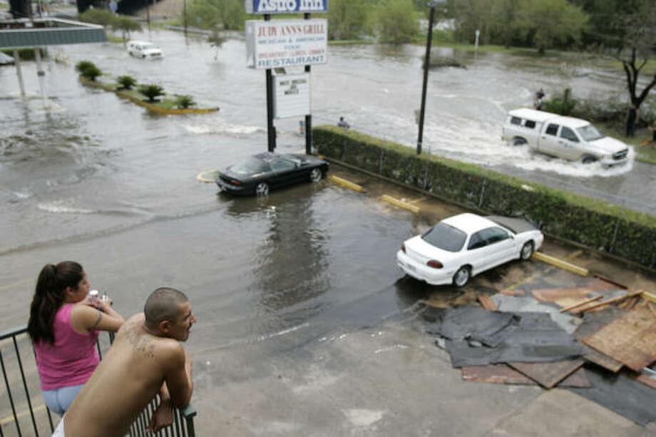 Rachel Ortiz, left, and Alex Gonzalez, 22,  look on as cars drive through flooded roads Sunday in Houston. Photo: Frank Franklin II, AP