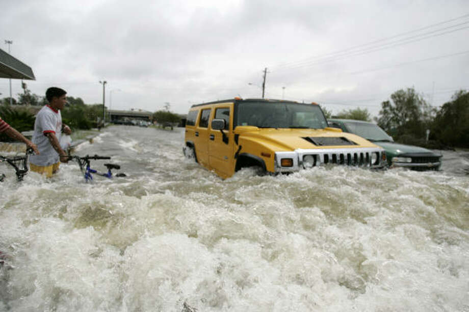 People look on as vehicles drive through roads flooded after Hurricane Ike Sunday in Houston. Photo: Frank Franklin II, AP
