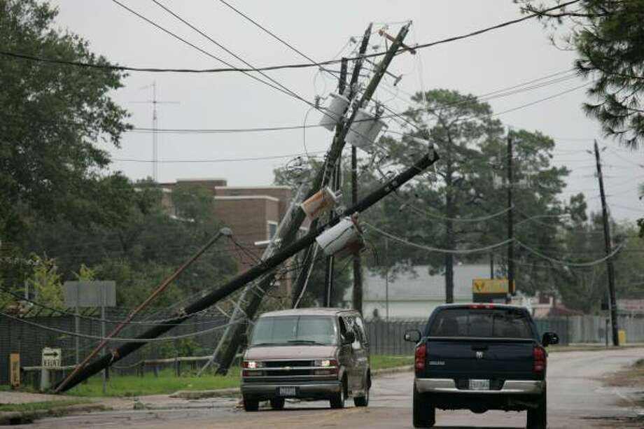 Motorists drive under downed power lines Sunday after Hurricane Ike swept through Houston. Photo: Marcio Jose Sanchez, AP