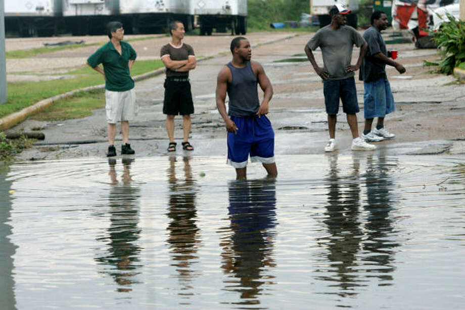 A group of men watches a traffic bottleneck on Interstate 10 caused by flooding Sunday. Photo: Marcio Jose Sanchez, AP
