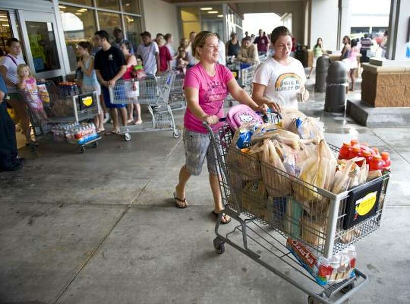 Two women push out a cart full of groceries at a League City Kroger.