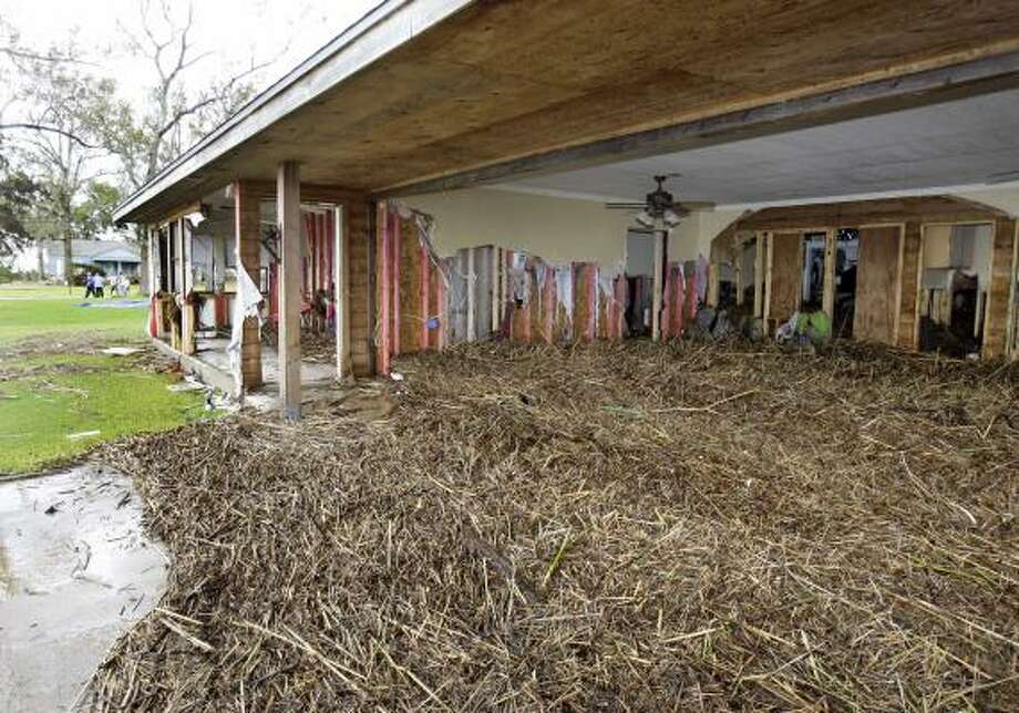 The first floor of a house is covered in marsh grass after Hurricane Ike in Bridge City, Texas, Sunday. Photo: Alex Brandon, AP
