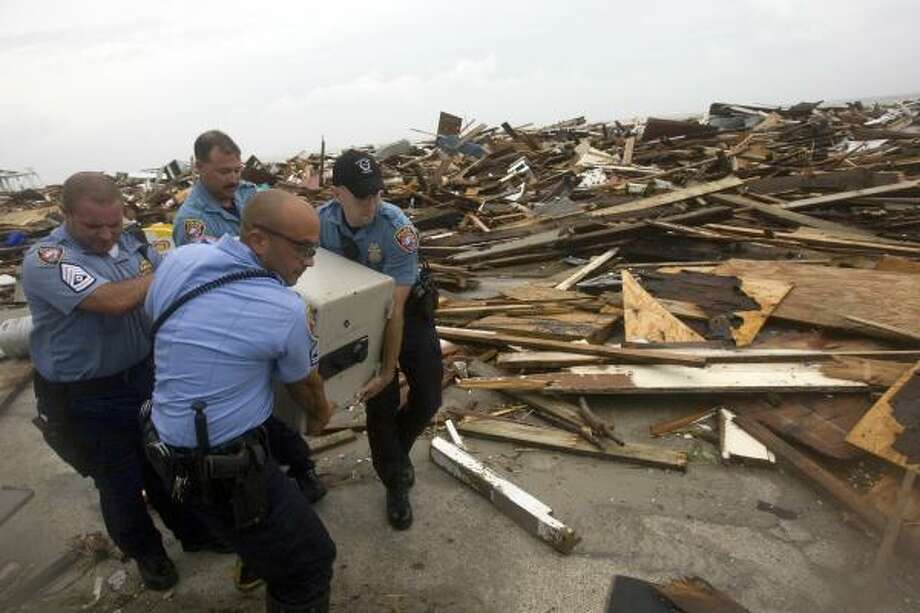 Galveston police officers remove a safe from the rubble where the Hooters restaurant was decimated by Hurricane Ike. Photo: Johnny Hanson, Chronicle