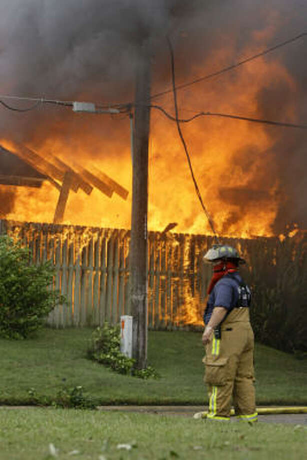 A Galveston firefighter works the scene of a blaze that has engulfed multiple townhomes. Photo: Matt Slocum, Associated Press
