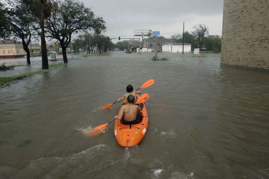 Brian Devall, top, 16, and his friend Andrew David, 17, paddle a kayak through a flooded street to check on Devall's house. Photo: Matt Slocum, Associated Press