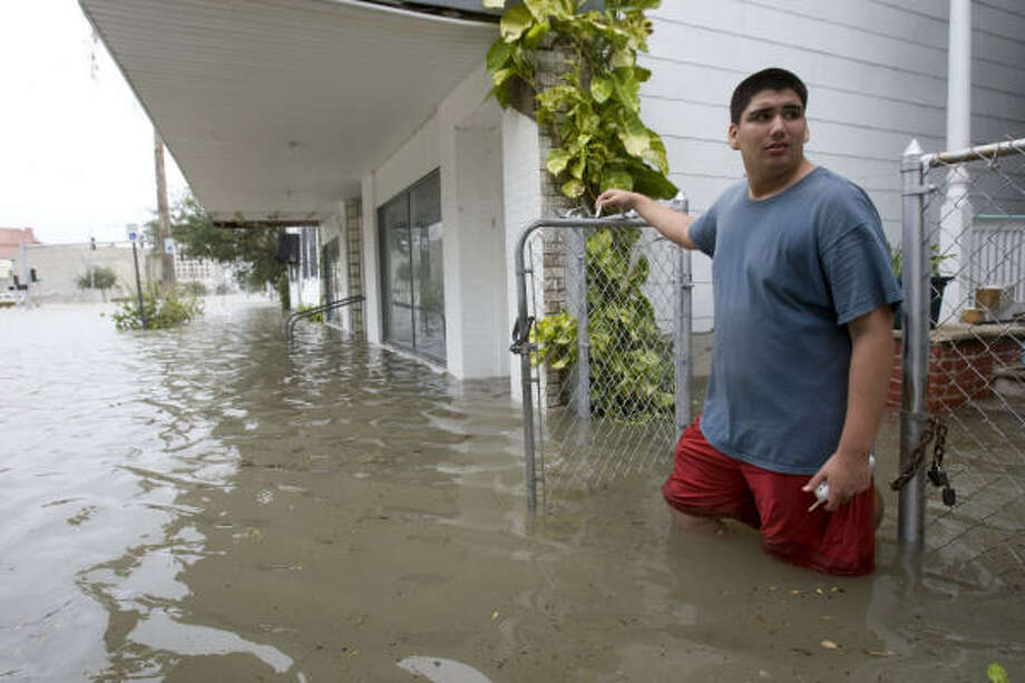 Sean Rumgay, 15, stands in floodwaters lapping up to his front door near the historic downtown area. Photo: Brett Coomer, Chronicle