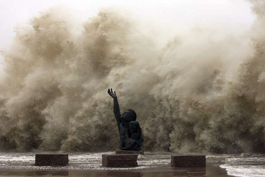Waves crashing into the Seawall reaches over the memorial to the Great Storm of 1900. Photo: Johnny Hanson, Chronicle