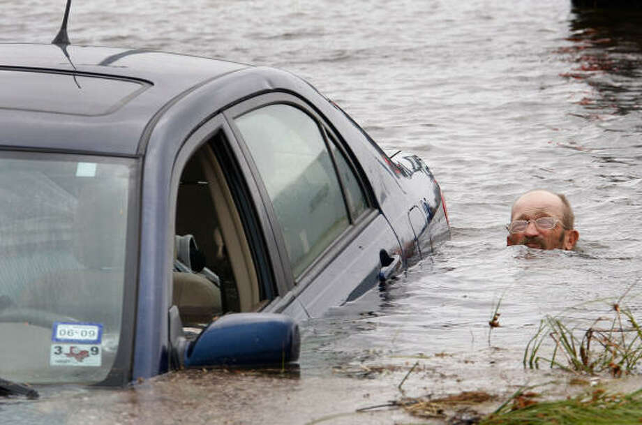 A man tries to rescue a car that was swept away by floodwater caused by Hurricane Ike while trying to evacuate. Photo: Scott Olson, Getty Images
