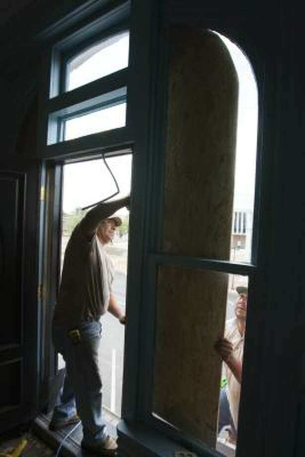 Maricio Hernandez, left, and Antonio Azana place protective plywood on windows of a business in preparation for Hurricane Ike Thursday, Sept. 11, 2008, in downtown Bay City, Texas. Photo: Brett Coomer, Chronicle