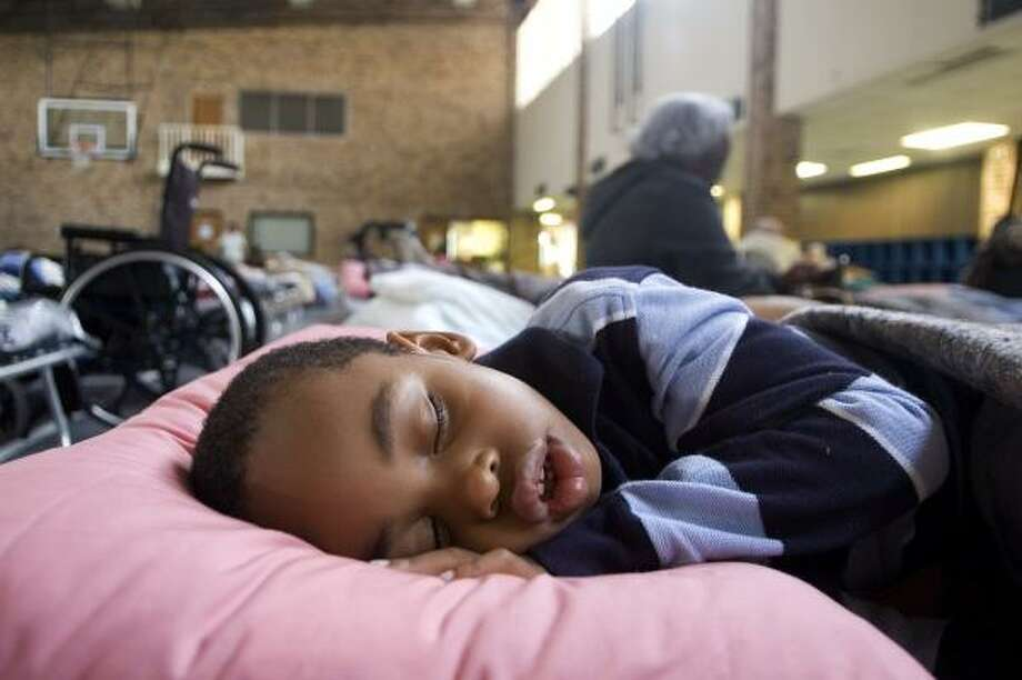 Next to nearly 40 other evacuees, Zaylan Shaffer, 4, sleeps on a cot in the Killeen Community Center on Sept. 11. Shaffer, from Ontario, Canada, was on vacation with his family in Bay City when residents were asked to evacuate the area. Photo: Sarah Moore Kuschell, Killeen Daily Herald