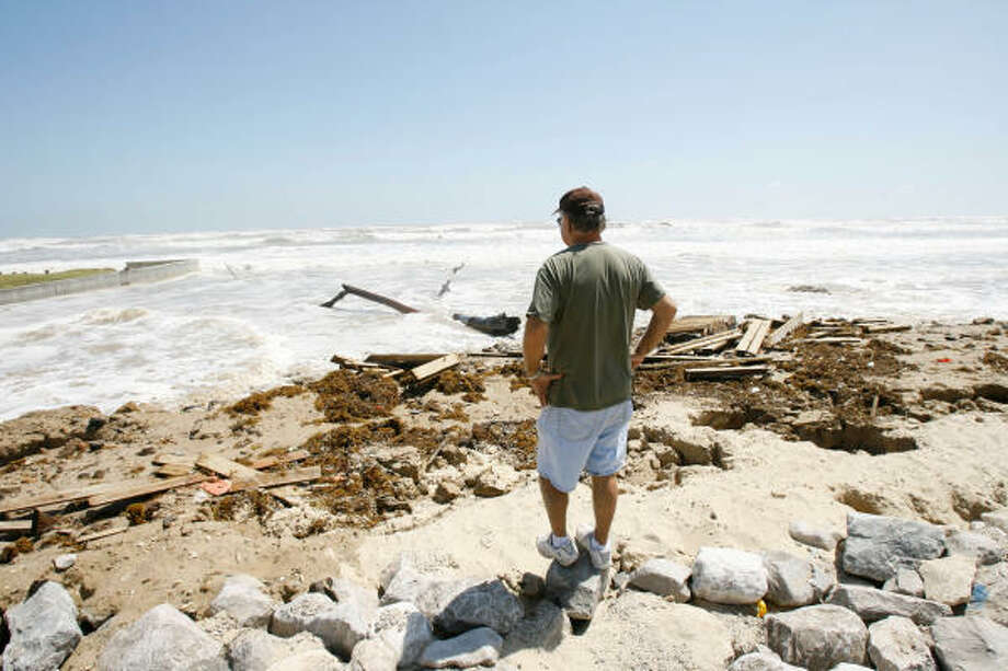 Billy Proske, a year-round resident of Surfside Beach, watches water creep over a seawall of boulders as he gets ready to leave. Proske says he doesn't expect to come back to his house after the 15 foot surge. Photo: Nick De La Torre, Chronicle
