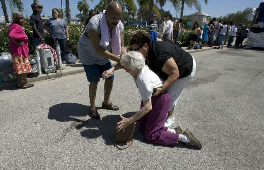 Galveston resident Elizabeth Schadt is helped up after falling as hundreds waited for buses that would take them to a shelter in Austin from the Island Community Center in preparation of Hurricane Ike in Galveston. Photo: Johnny Hanson, Chronicle