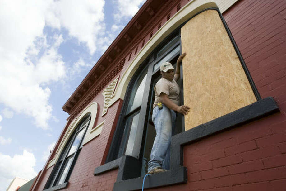 Maricio Hernandez leans out a second-story window to place protective plywood on windows of a business in preparation for Hurricane Ike in downtown Bay City. Photo: Brett Coomer, Chronicle