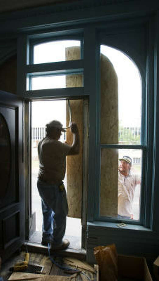 Maricio Hernandez, left, and Antonio Azana place protective plywood on windows of a business in preparation for Hurricane Ike in Bay City. Photo: Brett Coomer, Chronicle