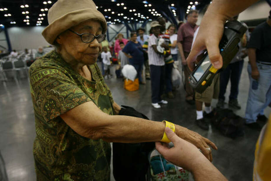 Minnie Thompson, 80, waited most of the day to be evacuated from Webster and she is finally scanned to board the bus bound to Mesquite. Photo: Mayra Beltran, Chronicle