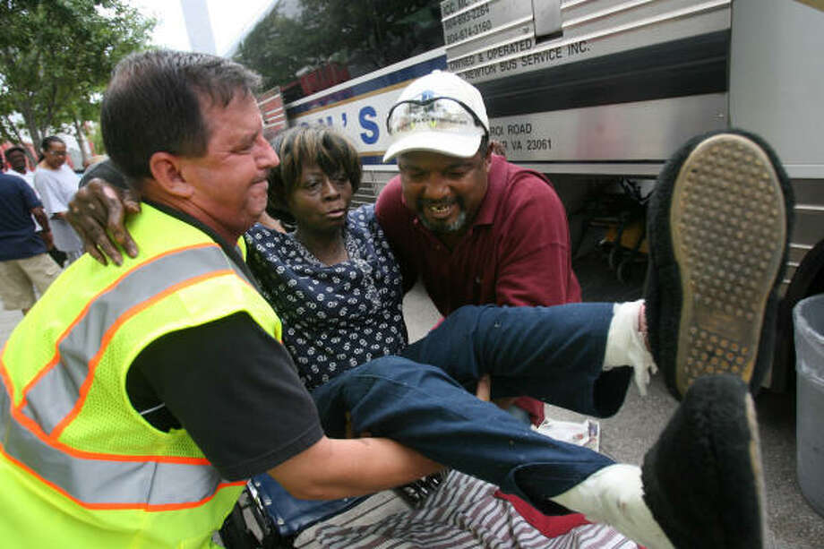 Margaret Augustine of New Orleans, a special needs evacuee from Webster, is lifted off her wheelchair by a volunteer and husband Joseph Augustine to board the bus bound to Mesquite. Photo: Mayra Beltran, Chronicle