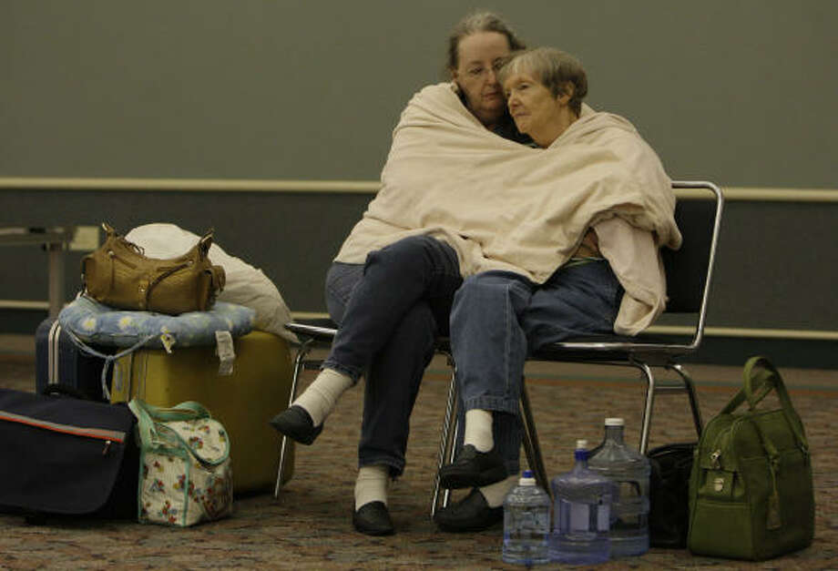Carole McFadden, left, and her mother, Freda Evans of Friendswood wait together to be evacuated by bus from Texas City. Photo: Melissa Phillip, Chronicle