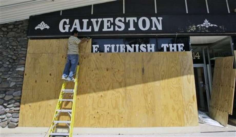 Adrian Demetreo boards the windows of Galveston Furniture today in Galveston. Photo: David J. Phillip, AP