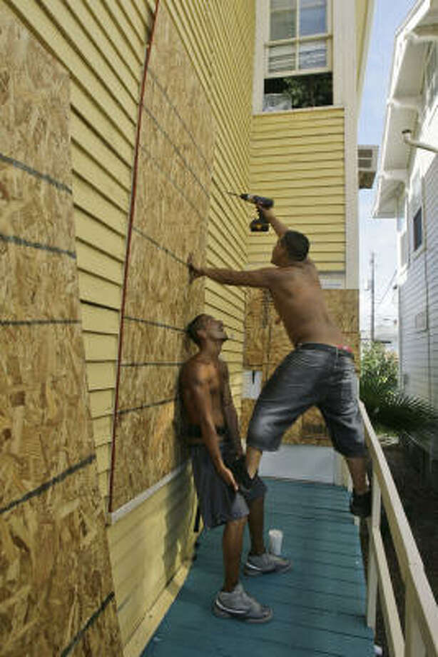 John Vasquez, left, and Lance Shunkwieler board up a home today in Galveston as Hurricane Ike approaches the Texas coast. Photo: Matt Slocum, AP