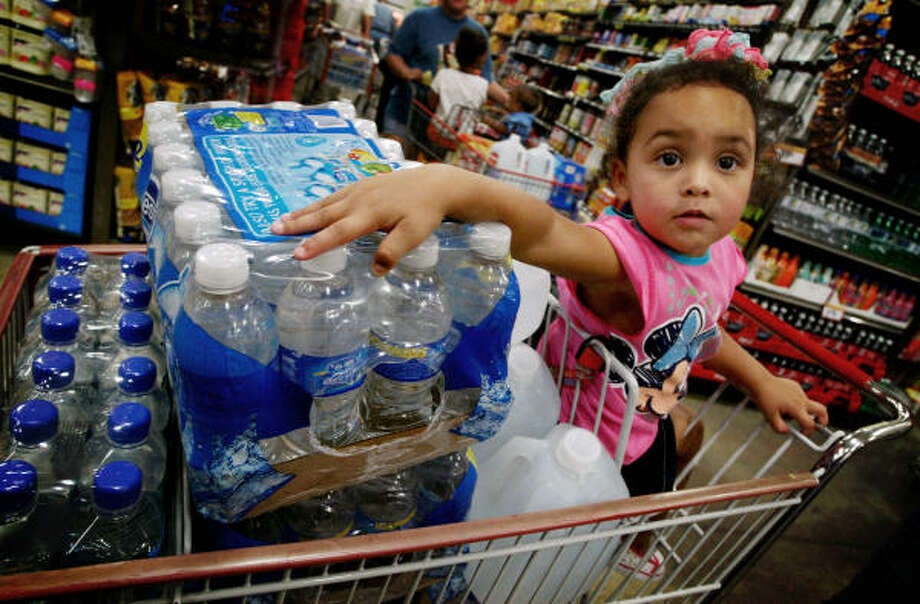 Ciara Bedford, 2, accompanies her mother to the supermarket as they stock up on water in Victoria. Photo: Roni Gendler, AP