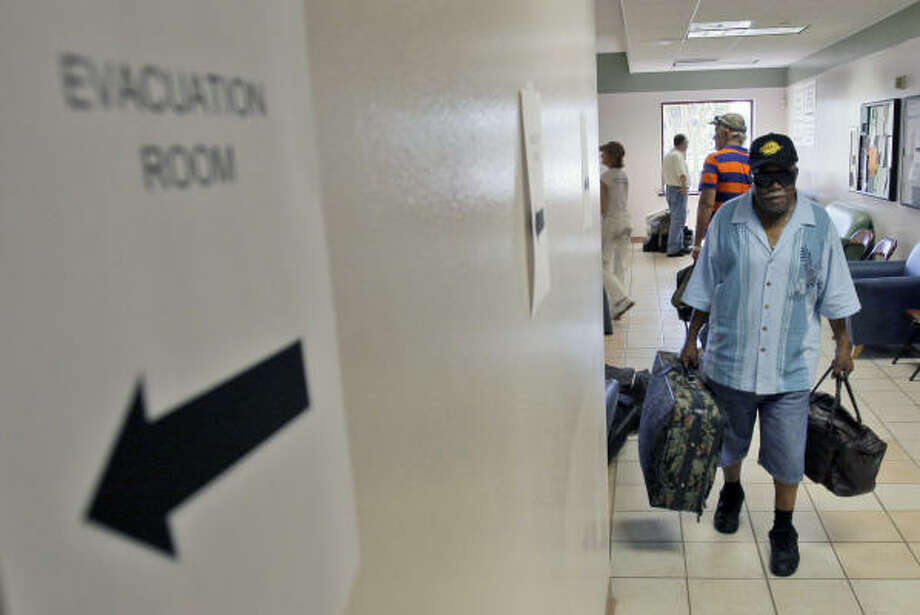 Willis Porter carries his bags as he waits to sign up to board a bus at an evacuation center on Galveston Island. Photo: David J. Phillip, AP