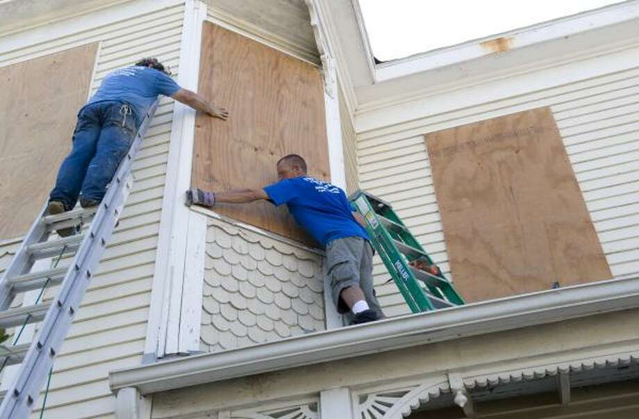 Chris Robertson, right, and John Moore board up a home, built in 1895. Photo: Dave Einsel, Getty Images