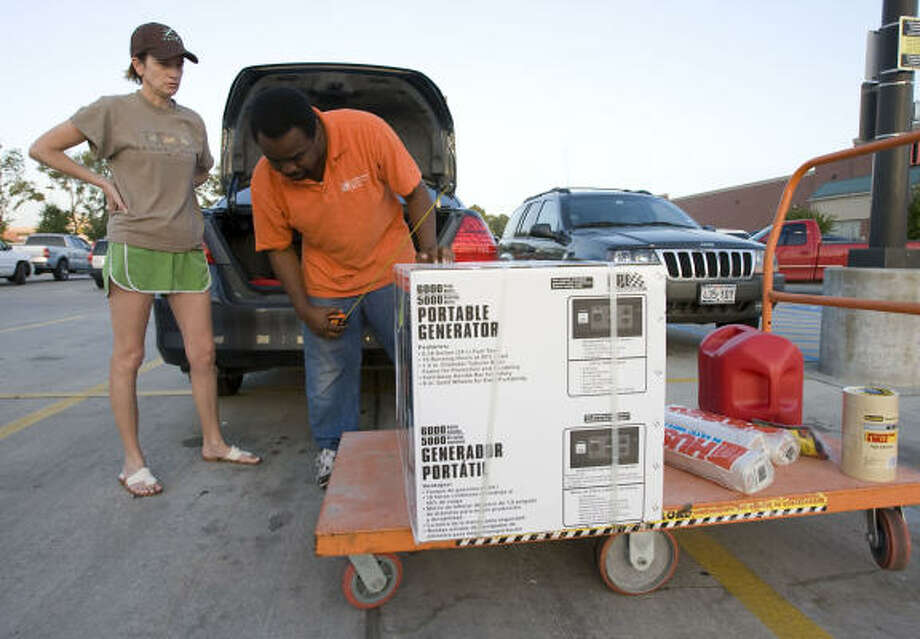 The Home Depot's Fred Felder, right, measures a generator box for Johnna Van Keuren as she buys supplies in preparation for Hurricane Ike. Van Keuren was shopping today at a Home Depot store on I-10 near Wirt Road. Photo: James Nielsen, Chronicle