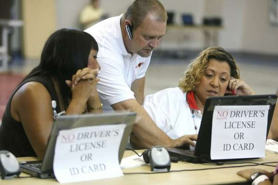 City of Corpus Christi employees Virginia Davis, left, and Robina Ramos, right, get help with the registration system for evacuees from Hurricane Ike from EWA Governmental Systems Inc. employee Tom Bock  as they register individuals at the Corpus Christi Gym in Corpus Christi, Texas,  on Thursday, Sept. 11, 2008. Photo: Rachel Denny Clow, AP