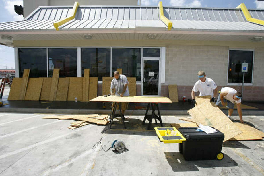 Tailored Door and Glass employees board up a McDonald's with wood on Sept. 10 in Freeport. Photo: Nick De La Torre, HOUSTON CHRONICLE