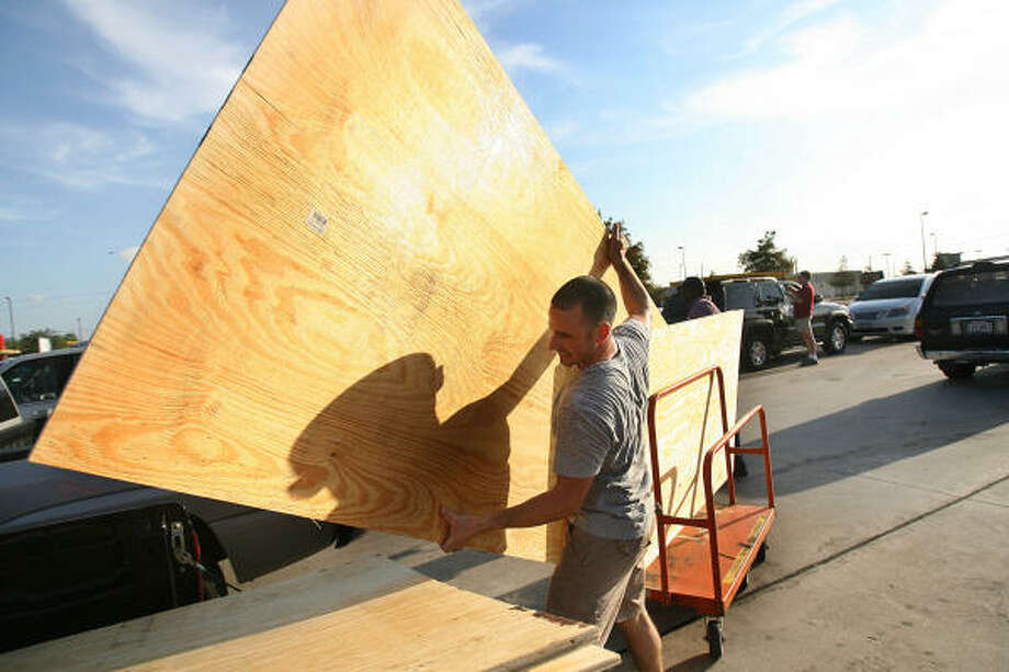 """I am getting ready before everyone gets home from work, and figures out that the hurricane is come this way"" says Eric Trevino, of Pearland, as he loads the plywood to his truck outside the Home Depot in Pearland on Sept. 10. Photo: Mayra Beltran, Houston Chronicle"