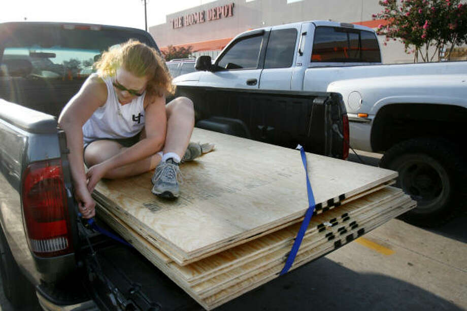 Angie Kleman, of Pearland, ropes down the plywood to the bed of her truck outside the Home Depot as residents of the northern section of Brazoria County prepared for Hurricane Ike on Sept. 10 in Pearland. Photo: Mayra Beltran, Houston Chronicle