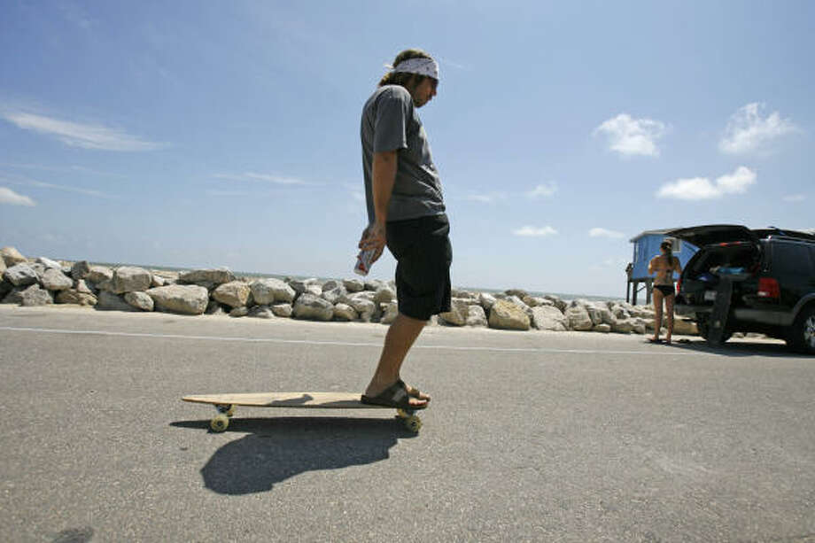 While other residents prepare for Ike, Wesley Burnett, of Dallas, clowns around on his skateboard while waiting for the waves to build in Surfside Beach on Sept. 10. Photo: Nick De La Torre, HOUSTON CHRONICLE