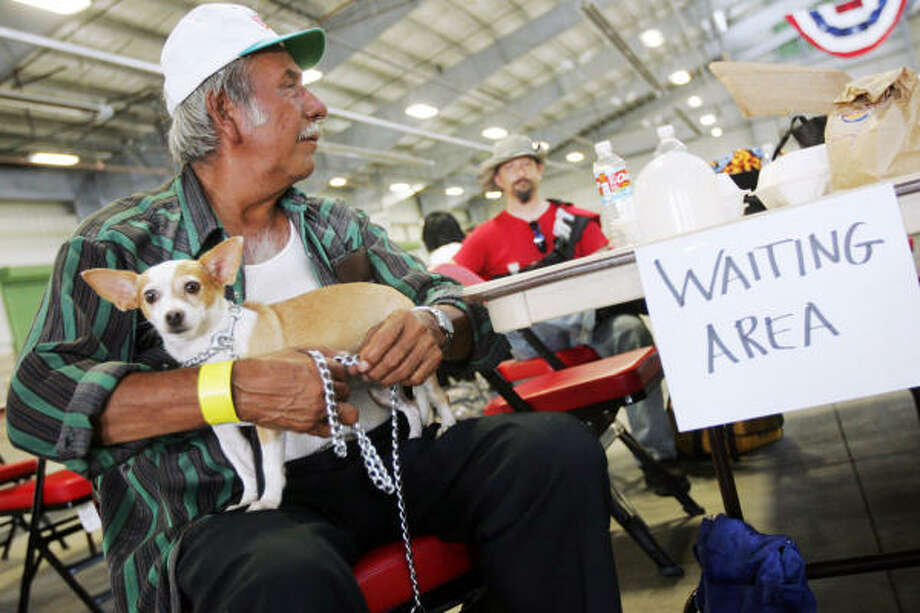 Juan Rodriguez of Robstown sits with his Chihuahua, Margarita, as he waits for the buses to load Wednesday at the regional fairgrounds in Robstown. Photo: Michael Zamora, Corpus Christi Caller-Times