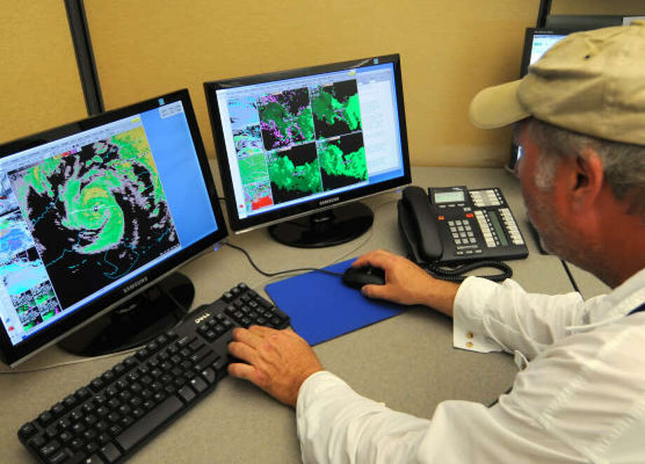 Andrew Devanas, a science and operations officer at the Key West National Weather Service office monitors Hurricane Ike Tuesday in Key West, Fla. The storm caused some 900,000 Cubans to be evacuated. Photo: Handout, Getty Images