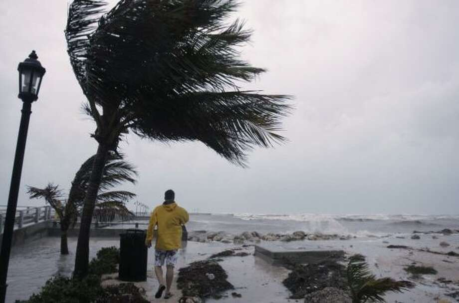 A man walks along the White Street pier as waves crash in Key West, Fla. Tuesday. Photo: Lynne Sladky, AP
