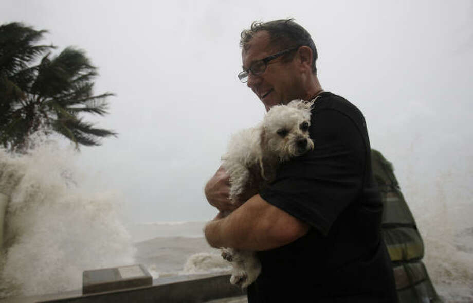 Andrew Davies walks with his dog Gucci as waves crash at the Southernmost Point in Key West, Fla. Tuesday. Hurricane Ike is passing to the south over Cuba. Photo: Lynne Sladky, AP