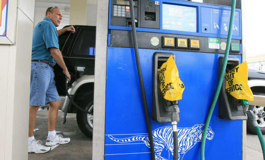 "Paul Finzel fills up his vehicle with gasoline at a Stripes in Corpus Christi. The station had bags over several of its fuel dispensers Tuesday morning, despite having just received fuel. ""I'm gassing up just in case I need to get out,"" Finzel said. Photo: Rachel Denny Clow, AP"