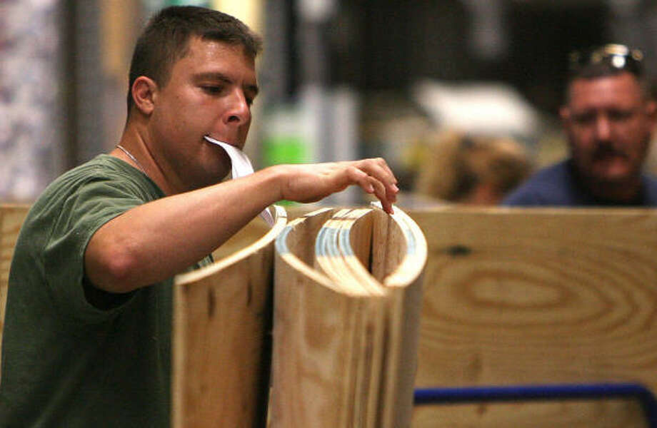 Gene Trelles counts his pieces of plywood after loading them onto a cart Tuesday at Lowe's in Corpus Christi. Photo: Todd Yates, AP