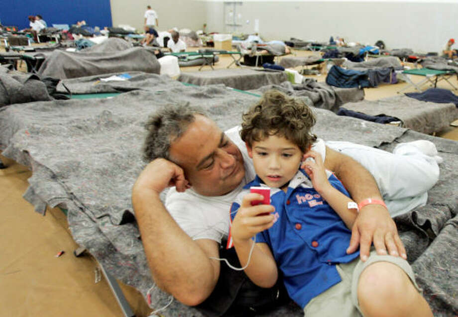 Jorge Fermin Sarut looks at his son Tristan, 8, as he listens to his iPod at a Red Cross Shelter in Miami, Sept. 8. Photo: Alan Diaz, AP