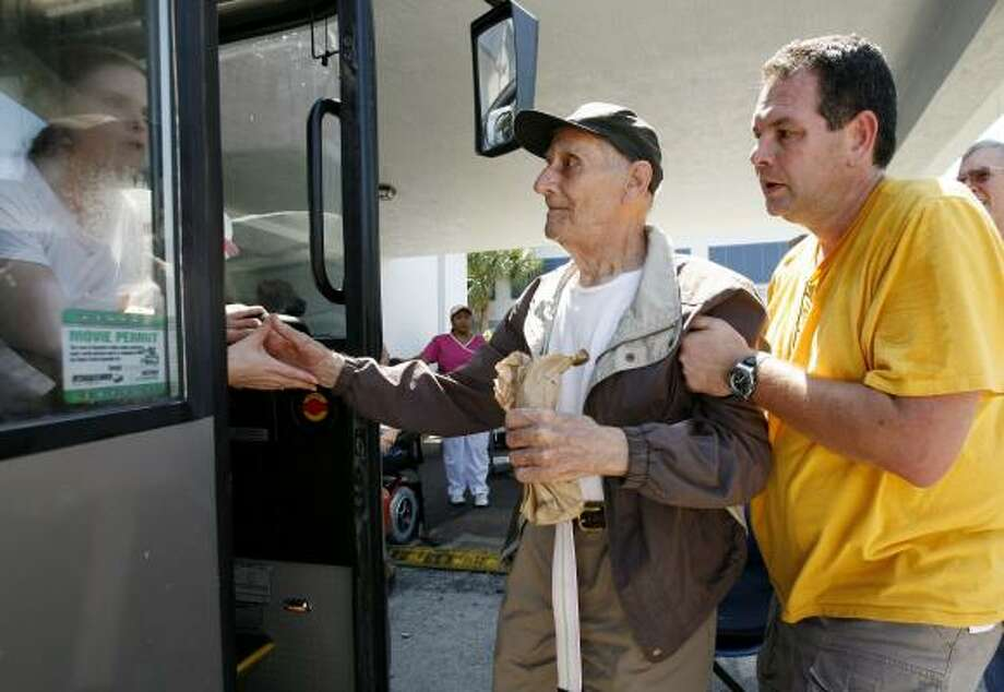 Ed Cohen, 87,  is helped onto a bus by Dan Colombini  as residents are evacuated from the Key West Convalescent Center in Key West, Fla. Sept. 7. Photo: Lynne Sladky, AP