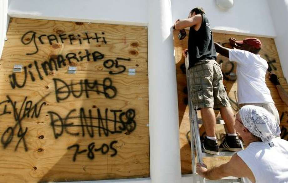 Preparing for Ike in in Key West, Fla., Sept. 7, Pedja Dordevic, left, puts up plywood bearing the names of past hurricanes. Photo: Lynne Sladky, Associated Press