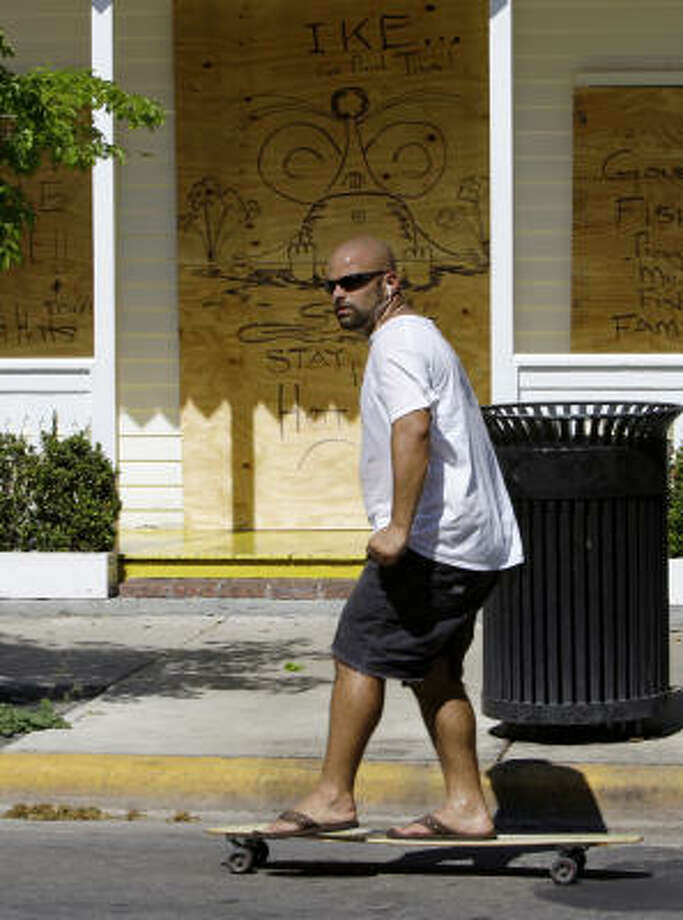 "A man on a skateboard rides past a boarded-up business with a sign that reads ""Ike, Go Find Tina"" in Key West, Fla., on Sept. 7. Photo: Lynne Sladky, Associated Press"