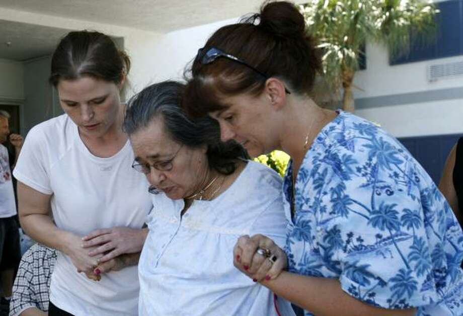Christy Hoskins, left, and Ginny Matea, right, help a resident of the Key West Convalescent Center board a bus for evacuation on Sept. 7. Photo: Lynne Sladky, Associated Press
