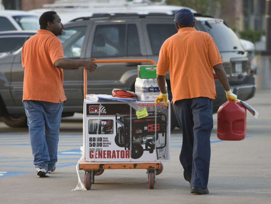 Home Depot employee Fred Felder, left, and an unidentified employee wheel a cart of supplies for Hurricane Ike to a customer's car today in Houston. Photo: James Nielsen, Chronicle
