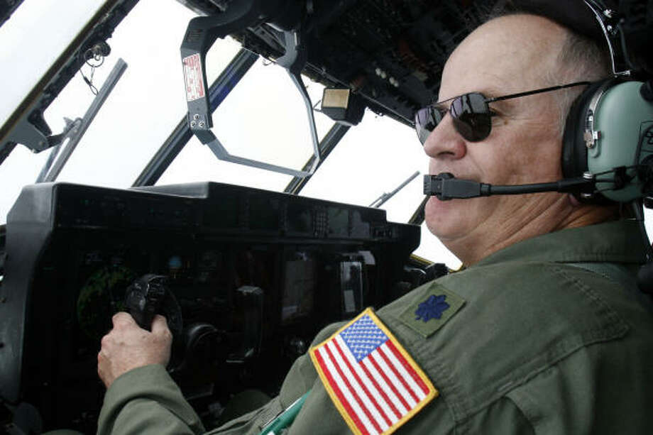 Pilot Lt. Col. Mark Carter speaks to other crew via his headset as he directs the Hurricane Hunters' C-130J into Hurricane Ike over the Gulf of Mexico. Photo: Rogelio V. Solis, AP