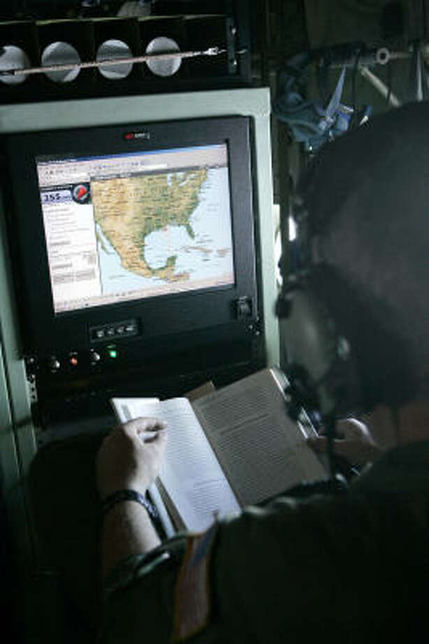 With his monitor tracking their flight, Tech. Sgt. Scott Blair uses the quiet time before flying into Hurricane Ike to try to read from a book he has brought along for the Hurricane Hunters' mission . The Air Force Reserve C-130J's only non-officer, Blair has several roles including loadmaster and preparing and releasing a sensor-laden tubes into various areas of the hurricane. Photo: Rogelio V. Solis, AP