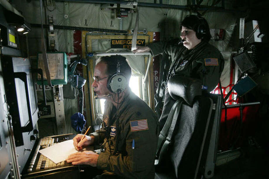 Flight meteorologists Lt. Col. Rich Harter, seated, and Maj. Deeann Lufkin review information being fed them from dropsondes, sensor-laden tubes, that are released into various parts of Hurricane Ike to provide the Hurricane Hunters' with valuable weather information. Photo: Rogelio V. Solis, AP