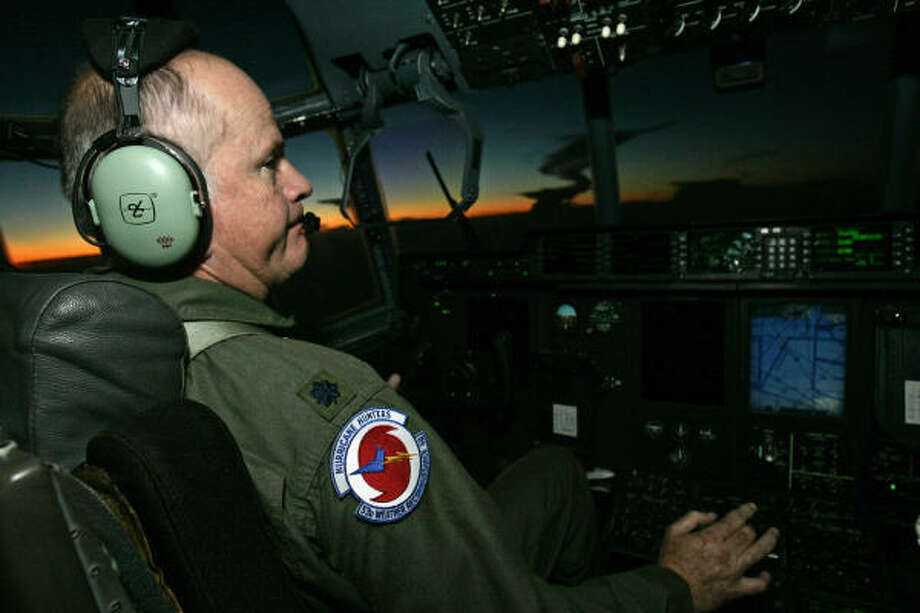 Pilot Lt. Col. Mark Carter speaks to other crew via his headset as he directs the Hurricane Hunters' Air Force Reserve C-130J aircraft back to its home at Keesler Air Force Base. Photo: Rogelio V. Solis, AP